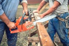Trabajadores, manitas que cortan la madera de la madera usando la motosierra mecánica Foto de archivo libre de regalías