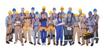 Trabajadores manuales confiados contra el fondo blanco imagenes de archivo
