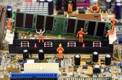 Trabajadores miniatura que instalan la memoria RAM Imágenes de archivo libres de regalías