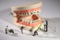Trabajadores miniatura que realizan procedimientos dentales Oficina dental AR Fotos de archivo