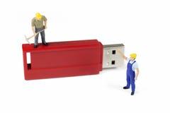 Trabajadores miniatura que trabajan en memoria USB foto de archivo