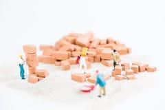 Trabajadores miniatura que trabajan junto en la colocación de ladrillos Foto de archivo