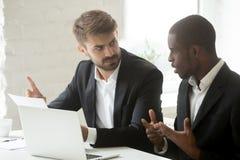 Trabajadores multiétnicos que discuten sobre la documentación de papel durante mee foto de archivo