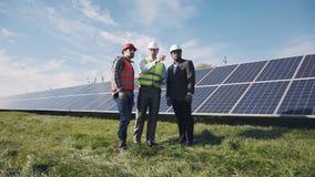 Trabajadores que caminan adentro al lado de la fila de los paneles solares