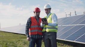 Trabajadores que caminan entre filas de los paneles solares Fotografía de archivo