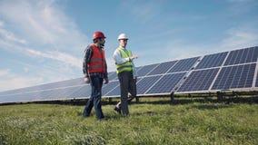 Trabajadores que caminan entre filas de los paneles solares Imágenes de archivo libres de regalías
