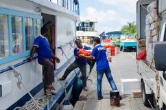Trabajadores que cargan mercancías en barco de la fuente Foto de archivo libre de regalías