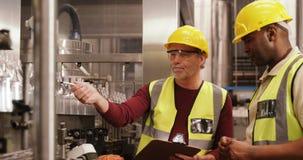 Trabajadores que comprueban las botellas en cadena de producción