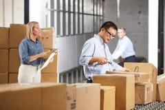 Trabajadores que comprueban mercancías en la correa en la distribución Warehouse Imágenes de archivo libres de regalías
