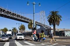 Trabajadores que cruzan la calle en el embarcadero veintiocho, debajo del puente San Francisco del oackland, California Foto de archivo