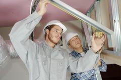 Trabajadores que erigen los paneles del aislamiento de la pared en emplazamiento de la obra Imagen de archivo libre de regalías