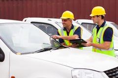 Trabajadores que examinan los coches imagenes de archivo