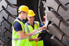 Trabajadores que examinan los neumáticos Imágenes de archivo libres de regalías