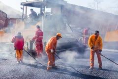 Trabajadores que hacen el asfalto con las palas en el camino Fotos de archivo libres de regalías