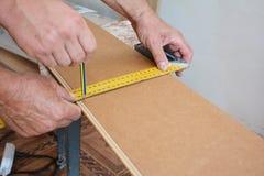 Trabajadores que instalan el suelo laminado de madera y que miden al tablero laminado antes de cortar imagen de archivo