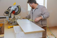 Trabajadores que instalan la lamina y que miden estantes blancos laminados antes del corte foto de archivo libre de regalías