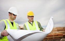 Trabajadores que leen planes de la construcción