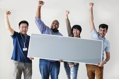 Trabajadores que mantienen al tablero en blanco unido foto de archivo libre de regalías