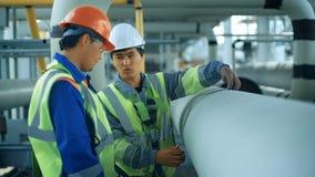 Trabajadores que miden un tubo con una cinta métrica Tierra trasera industrial con pipiline del gas metrajes