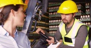 Trabajadores que obran recíprocamente con uno a en fábrica metrajes