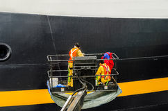 Trabajadores que pintan el estribor de un barco de cruceros Imágenes de archivo libres de regalías
