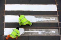 Trabajadores que pintan el paso de peatones imagen de archivo libre de regalías