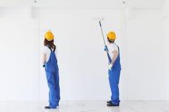 Trabajadores que pintan la pared imagen de archivo libre de regalías