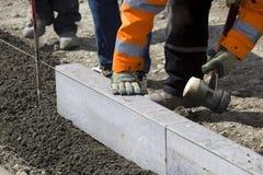 Trabajadores que ponen las losas del granito Imagen de archivo