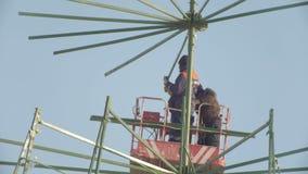Trabajadores que reparan la construcción en alto lugar - haciendo el pino del Año Nuevo para celebre, ciérrese para arriba almacen de video