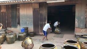 Trabajadores que ruedan las macetas grandes del dragón fuera del horno ardiente almacen de metraje de vídeo