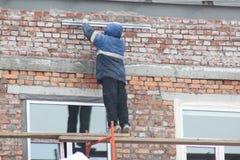 Trabajadores que se colocan en una escalera de madera en el bosque, reparando la pared del edificio imagen de archivo