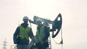 Trabajadores que se levantan en un fondo de la torre de perforación de aceite, cierre metrajes