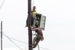 Trabajadores que suben en línea de transmisión concreta eléctrica del polo Fotos de archivo libres de regalías