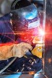 Trabajadores que sueldan con autógena la construcción por la soldadura de MIG Imagenes de archivo