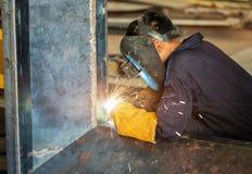 Trabajadores que sueldan con autógena la construcción por la soldadura de MIG Foto de archivo libre de regalías