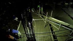 Trabajadores que trabajan en horas extras en la noche durante la colada concreta almacen de video