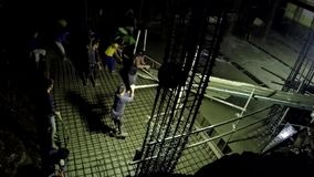 Trabajadores que trabajan en horas extras en la noche durante la colada concreta almacen de metraje de vídeo