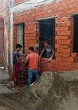 Trabajadores que trabajan en un lado de la construcción Imagenes de archivo