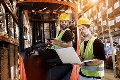 Trabajadores que usan la carretilla elevadora de la tecnología en almacén fotografía de archivo
