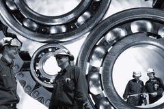 Trabajadores siderúrgicos con los engranajes y los transportes foto de archivo libre de regalías