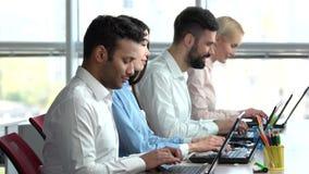Trabajadores sonrientes del soporte técnico que mecanografían en los ordenadores portátiles