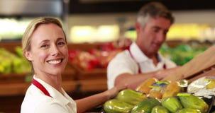 Trabajadores sonrientes que almacenan verduras metrajes