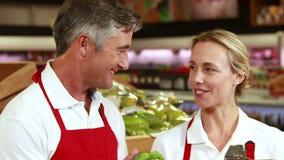 Trabajadores sonrientes que comprueban verduras almacen de metraje de vídeo
