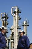 Trabajadores y refinería del petróleo foto de archivo