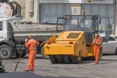 Trabajadores y rodillo del asfalto, reparación del camino Foto de archivo libre de regalías