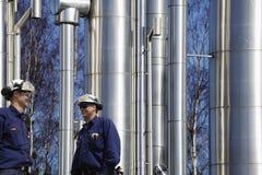 Trabajadores y tuberías de la refinería fotos de archivo
