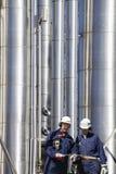 Trabajadores y tuberías de la refinería imagenes de archivo