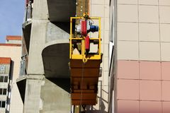 Trabaje con la cuna suspendida del frente dos amarillos con los trabajadores en un edificio alto nuevamente construido fotografía de archivo libre de regalías