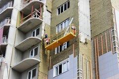 trabaje con la cuna suspendida frente amarillo en un edificio alto nuevamente construido imagenes de archivo