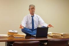 Trabaje el alivio de tensión relacionado con yoga como el hombre presenta con las pilas de papeleo y de ordenador en la mesa de r Imagen de archivo